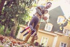 Fadern har lek med barn på trädgården, på flyttningen Royaltyfri Foto