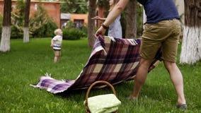 Fadern i bruna kortslutningar och blå skjorta fördelar plädet för picknick Den lyckliga modern spelar med hennes lilla son på stock video