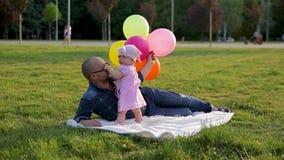 Fadern i exponeringsglas med ballonger och lögnen för begynnande dotter på filten parkerar in, då tar kysser dottern av exponerin stock video