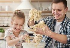 Fadern lagar mat bakelse med dottern fotografering för bildbyråer