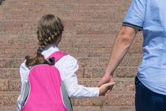 Fadern leder dottern med en ryggsäck på henne tillbaka till skolan Arkivbild