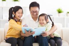 Fadern läste boken till barn Arkivfoto