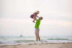 Fadern lyfter upp dottern på händer på solnedgånghavstranden med yach Royaltyfri Bild