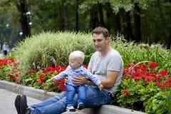 Fadern med årig son två i sommar parkerar royaltyfria bilder