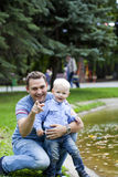 Fadern med årig son två i sommar parkerar arkivbild