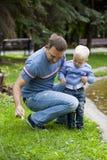 Fadern med årig son två i sommar parkerar royaltyfria foton