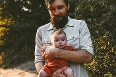 Fadern med behandla som ett barn att g? i familj f?r skog tillsammans arkivbild