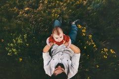Fadern med behandla som ett barn barnet som ligger på livsstil för gräsfamilj royaltyfri bild