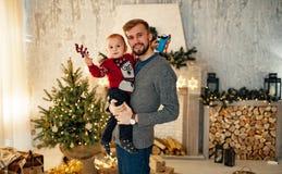 Fadern med hennes lilla son står mot bakgrunden av julgranen royaltyfri fotografi