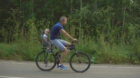 Fadern med sonen rider på cykeln i skogen stock video
