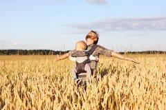 Fadern med spädbarnet behandla som ett barn i rem i fältet av korn Arkivfoton