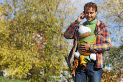 Fadern med spädbarnet behandla som ett barn i rem som talar på en mobiltelefon arkivbilder