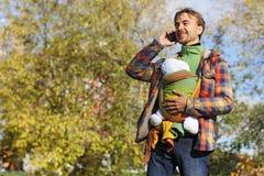 Fadern med spädbarnet behandla som ett barn i rem som talar på en mobiltelefon arkivbild