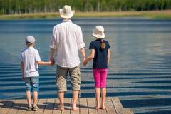 Fadern med två barn beundrar den härliga sceniska sjön, sikt royaltyfria foton