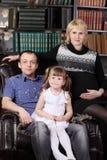 Fadern, modern och dottern sitter i fåtölj Royaltyfria Foton