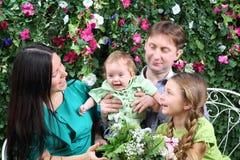 Fadern, modern och systern ser behandla som ett barn på bänk i trädgård Fotografering för Bildbyråer