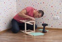 Fadern monterar en stol för barn arkivbild