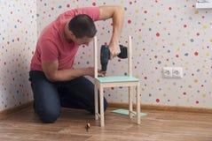 Fadern monterar en stol för barn royaltyfri foto