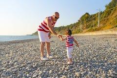 Fadern och 2 år son i liknande kläder går på sjösidan Arkivfoto