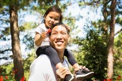 Fadern och barnet tar en gå till och med skogfarsan ger en ridtur på axlarnaritt royaltyfri fotografi