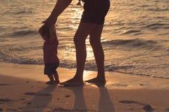 Fadern och behandla som ett barn lite dottern som går på sandstranden royaltyfria bilder