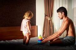 fadern och den lilla blonda flickan i rosa färger spelar pyramiden på soffan Royaltyfria Foton