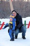 Fadern och den lilla sonen i vinter parkerar arkivfoton