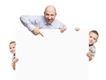 Fadern och det tomma sonsinnehav undertecknar eller affischerar royaltyfri bild