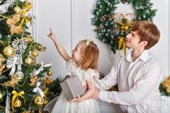 Fadern och dottern dekorerar julgranen arkivfoton
