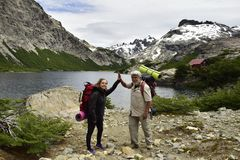 Fadern och dottern firar på kusten av en sjö som har avslutat för att gå arkivbild