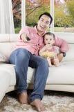 Fadern och dottern håller ögonen på roliga filmer på tv Arkivfoto