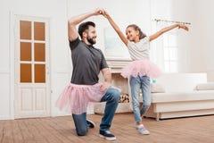 Fadern och dottern i rosa ballerinakjoltyll kringgår att dansa hemma Arkivbild