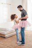Fadern och dottern i rosa ballerinakjoltyll kringgår att dansa tillsammans Arkivfoton
