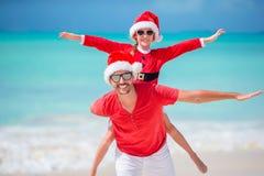 Fadern och dottern i Santa Hat har gyckel på den tropiska stranden arkivbilder