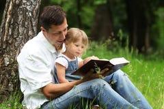 Fadern och dottern läser Royaltyfri Bild