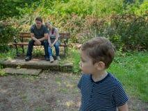 Fadern och dottern ser den störande sonen i förgrunden arkivfoton