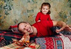 Fadern och dottern slåss för en gåva på sängen En flicka som rider en vuxen människa, försöker att ta en gåva arkivfoton