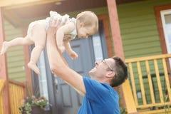 Fadern och dottern spelar framme av huset Royaltyfria Foton