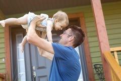 Fadern och dottern spelar framme av huset Royaltyfri Bild