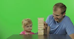 Fadern och dottern spelar jengaen Det lilla barnet drar träkvarter från torn stock video
