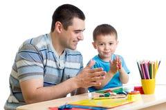 Fadern och hans barn har en rolig tidsfördriv med färgrika lekleraleksaker royaltyfri bild