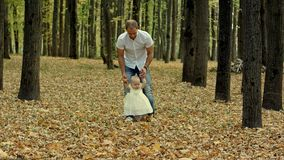 Fadern och hans behandla som ett barn gör första steg i höst att parkera royaltyfria foton