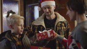 Fadern och hans lilla son ger gåvor för nytt år till deras fru, och modern och fadern kysser henne stock video