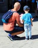 Fadern och hans lilla son håller ögonen på översikten royaltyfria bilder