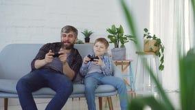 Fadern och hans ungt barn spelar videospelet på den hemmastadda soffan och att trycka på knäppas på styrspaken och samtal Lycklig stock video