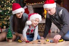 Fadern och modern med sonen spelar med det järnväg near julträdet för modellen Royaltyfri Bild