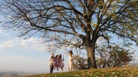 Fadern och modern skakar hennes döttrar på en gunga under ett träd stock video