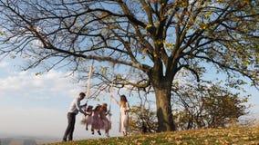 Fadern och modern skakar hennes döttrar på en gunga under ett träd lager videofilmer