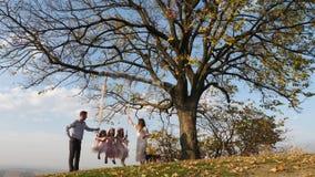 Fadern och modern skakar hennes döttrar på en gunga under ett träd arkivfilmer