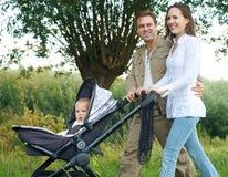 Fadern och modern som utomhus ler och går, behandla som ett barn i pram Fotografering för Bildbyråer